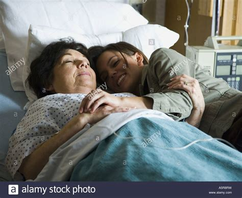 cuddle in bed woman cuddling in hospital bed with mature woman smiling