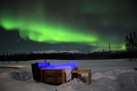 hotel under northern lights aurora bubble sled cing in the arctic under the