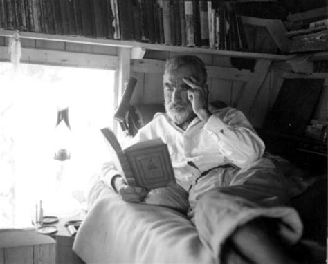 a in his home books hermit roy ozmer reading a book at his house pelican