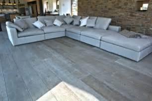 Living room with fabulous gray hardwood floor idea feat stone wall