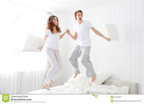 fun in bed happy couple jumping and having fun in bed stock photo