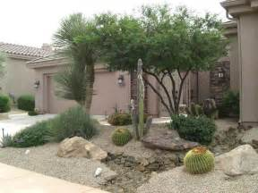 arizona desert front yard xeriscaping idea with a fake dry stream bed large decorative boulders