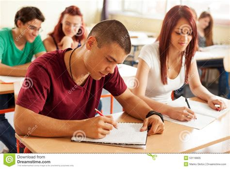 High School Writing Students At Desk