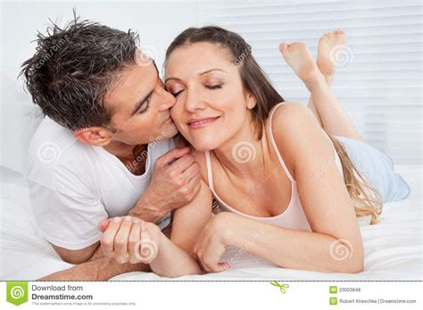 man and woman having sexuality in bed man kissing woman in bed royalty free stock photos image