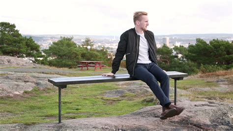 person sitting on a bench man sitting on a park bench in the cold stock footage