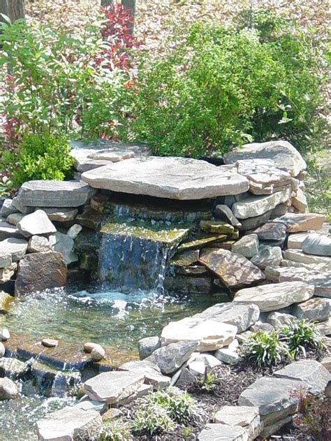 small pond waterfall with cantilevered rock and