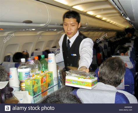 flight attendant on hainan airlines flight aircraft serving meal stock photo royalty free image