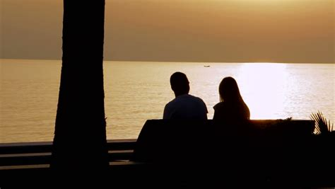bench couple watch young couple on a bench by the sea watching the sunset