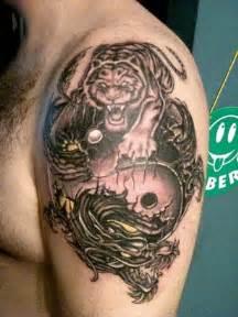 grey ink dragon and tiger tattoo on man left shoulder