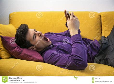 laying couch attractive young man using cell phone and yawning stock