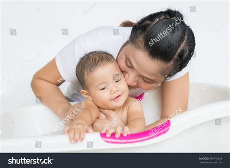 girl and boy kissing in bathroom happy baby taking bath playing mother stock photo