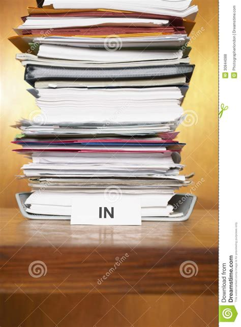 inbox with stack of paperwork on desk stock photo image