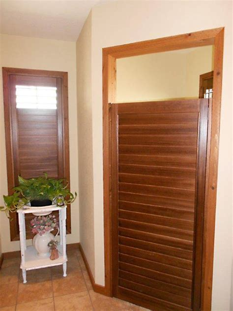Bathroom Saloon Doors by Stained Planation Shutters On A Rock Wall And Matching