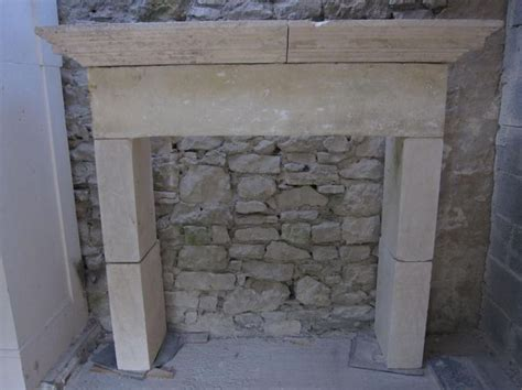 large and understated warm limestone fireplace from