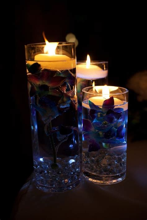wedding centerpieces with candles and water centerpieces in the blue dyed orchids submerged in