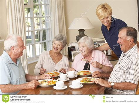 help with housing group of senior couples enjoying meal together in care