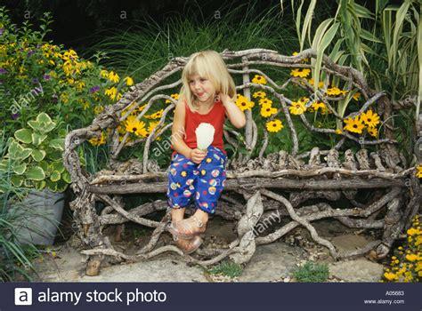 little girl sitting on bench statue little girl sitting on grapevine bench in flower garden