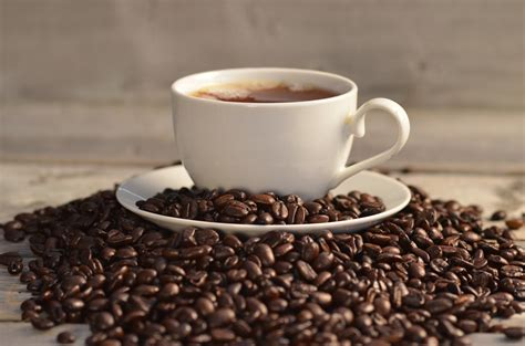 Coffee Di Coffee Bean coffee beans and cup on saucer between coffee beans on