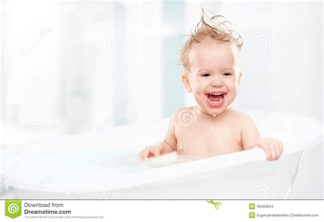 happy baby laughing and bathed in bath stock photo