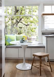 Sun filled kitchen window seat nook with white storage drawers topped