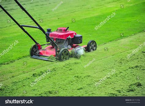 cutting grass games with a lawnmower lawn mower cutting green grass backyardgarden stock photo