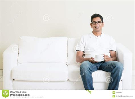 man sitting on couch asian man sitting on couch and drinking coffee stock photo