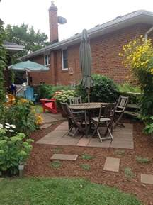 patio makeover on a budget fresh mulch and stepable thyme planted around patio stones