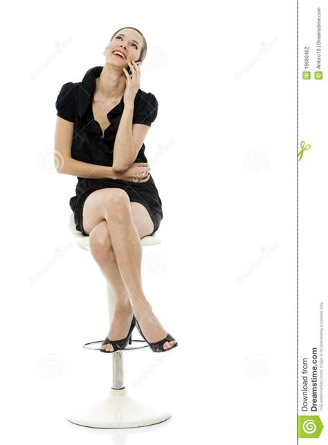 smart sitting on a stool holding a cellphone stock