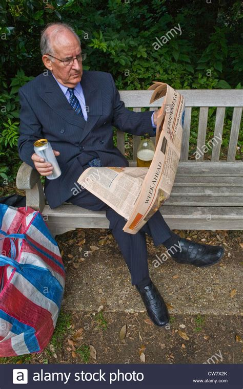 bench drinking businessman sitting on a park bench drinking beer reading