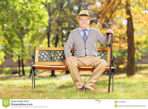 sitting in a park bench relaxed senior gentleman sitting on a wooden bench in a