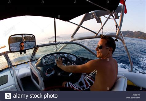 boat driving man man driving speedboat reflection in rear view mirror