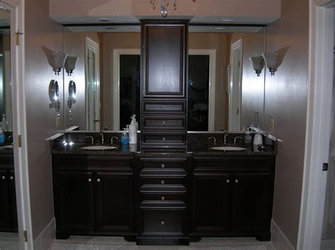 Black wooden vanity with high drawers and storage on the middle combined with black counter top