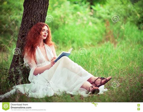 beautiful woman by the tree looking up stock photo image beautiful ginger woman sitting under tree and reading a
