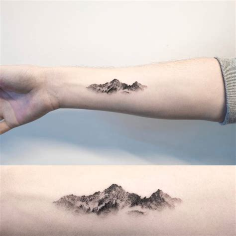 small guy tattoos mountain on the right inner forearm