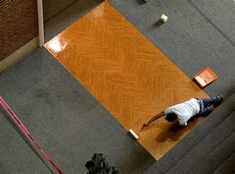 worker applying sealant to cork floor mockup two coats