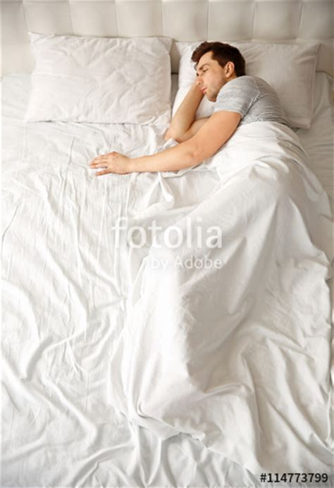 alone in bed quot young man sleeping alone in white big bed quot stock photo