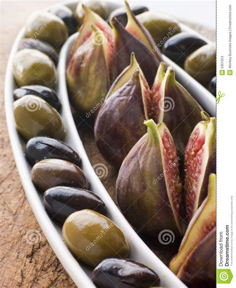 dish of green and black olives with fresh figs stock