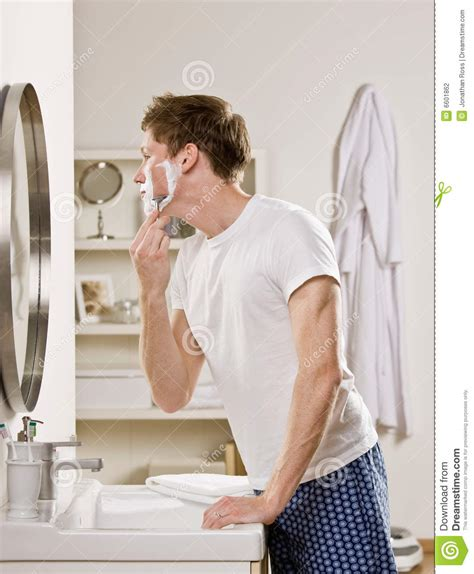 girl in bathroom with boy man in pajamas in bathroom shaving stock photography
