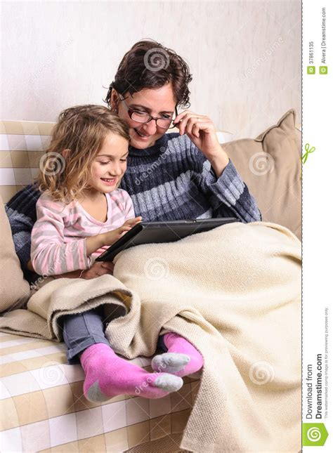 having on sofa child and mother using tablet on sofa royalty free stock