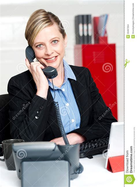 pretty front desk attending clients call stock images