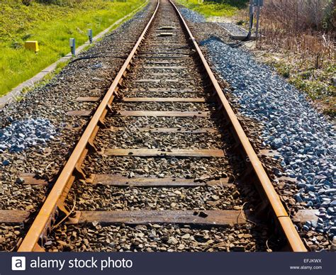 Sleepers Of Railway Track by Empty Railway Tracks Converging Into The Distance With