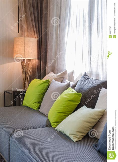 graues sofa grey sofa with green pillows in living room stock photo