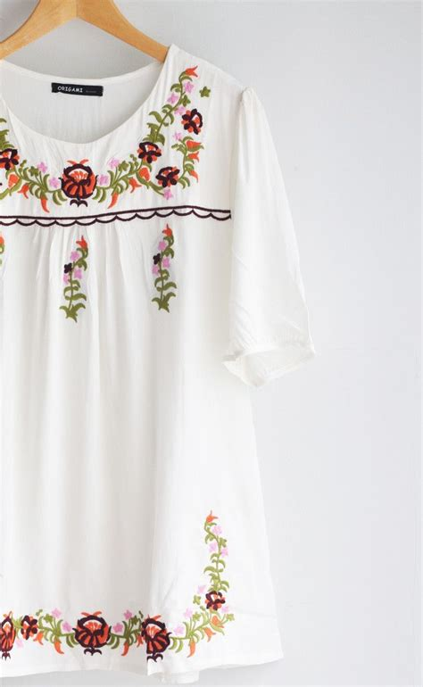 white one size fits all tunic with floral embroidery and sleeves that hit above the fits