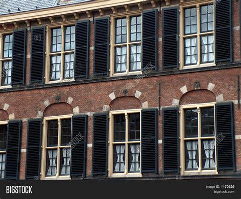 black shutter stylish windows with black shutters beige frames stock