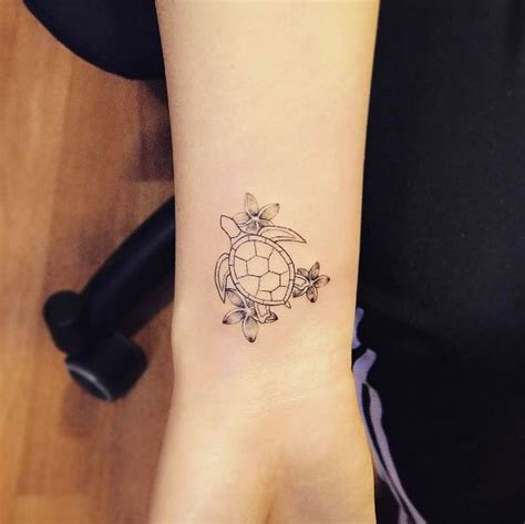 flowers and turtle tattoo on right wrist
