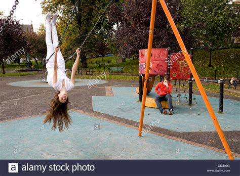 upside down swing teenage girl on swing in playground upside down stockfoto