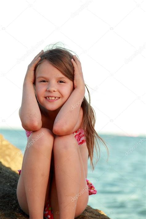 rainpow young little girls cute little girl in a bathing suit sitting on a large rock