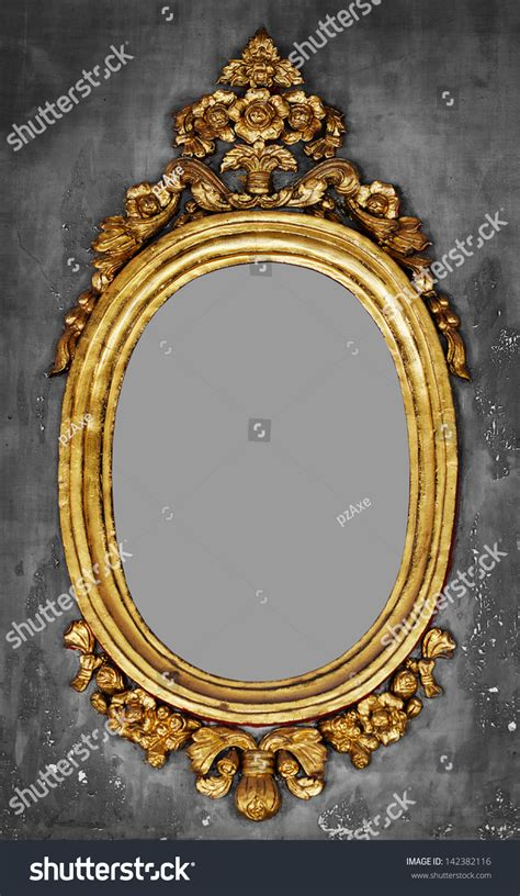 old fashioned oval gilt frame for a mirror on a gray