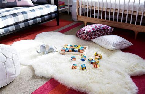 nursery sheepskin rug two tone crib next to guest bed transitional nursery