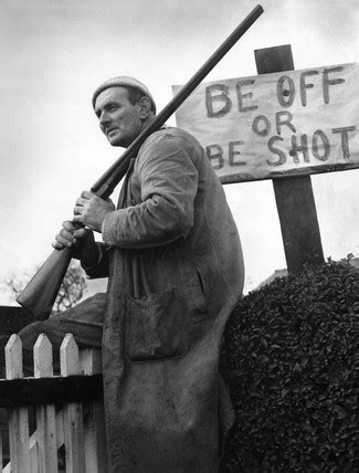 Farmer with gun sitting by 'Be Off or Be Shot' sign, 30